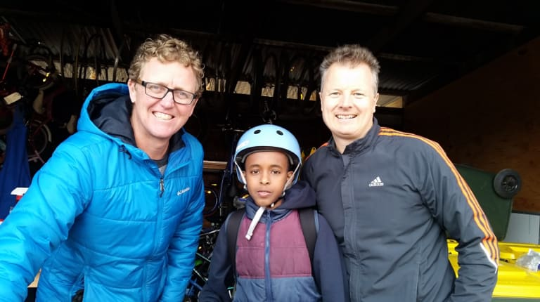 Student Safiol, 8, with Dr Cranky's Bikes for Kids founders Bart Sbeghen, left and Peter Hormann, right, at Flemington Primary School in 2016.