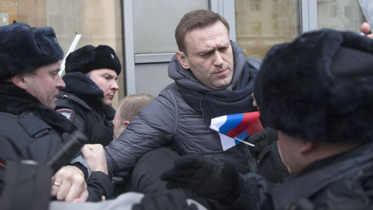 Russian opposition leader Alexei Navalny, centre, is detained by police officers in Moscow on Sunday. ,
