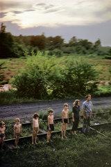 Seven people wait alongside the track.