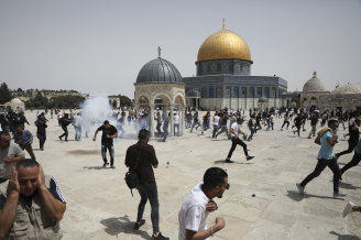 Palestinians run from sound bombs thrown by Israeli police in front of the Dome of the Rock shrine at al-Aqsa mosque complex in Jerusalem on Friday,
