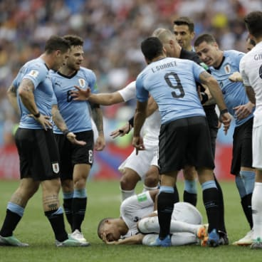 Someone find that sniper: Uruguay players fume after they believe France's Kylian Mbappe (on the ground) dived.