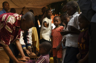 A child receives a blessing from a pastor during a prayer service for children in Kasai Central.
