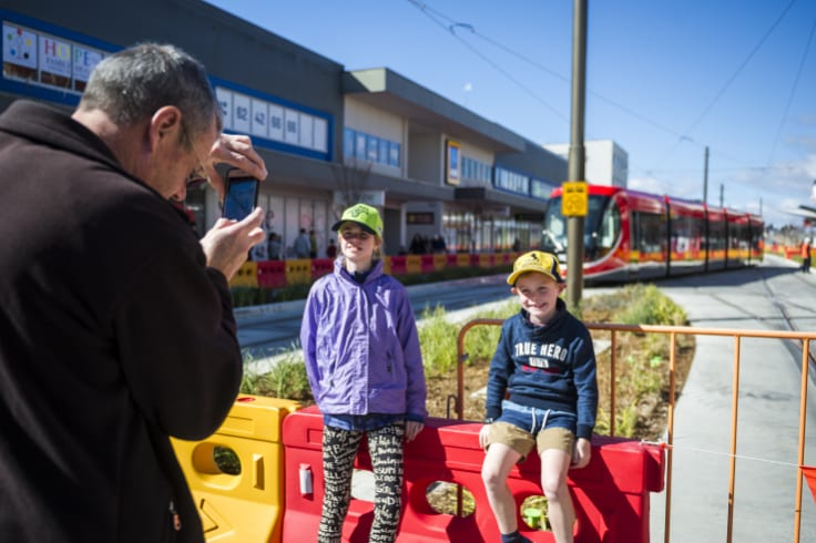 Angelique Corbitt, 10, and James Corbitt, 7, having their photo taken in front of the new tram.