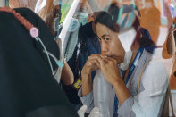 A woman blows air in a plastic bag to be tested for COVID-19 at Bali airport.
