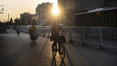Cyclists ride along a road as the sun sets in Beijing.