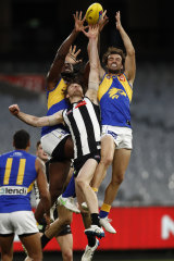 Nic Naitanui and Jack Petruccelle attempt to mark over Jordan Roughead of the Magpies.