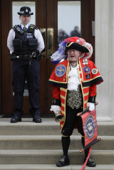 Self-styled town crier Tony Appleton announces the royal birthoutside the Lindo wing at St Mary's Hospital in London.