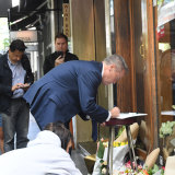 Federal Opposition Leader Bill Shorten writes in a card outside Pellegrini's cafe on Bourke Street, Melbourne.