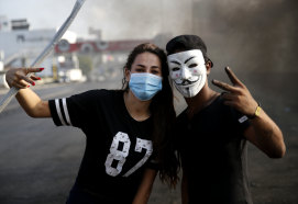 Protesters flash victory signs on Sunday as they block a highway linking Beirut to north Lebanon.