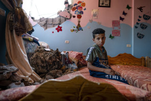 Ten-year-old Ibrahim sits in his bedroom in Beit Hanoun in the Gaza Strip. The room was damaged by an Israeli air strike that destroyed the neighbouring building in May.