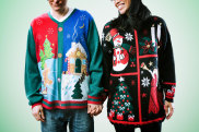 A man and woman wear ugly Christmas sweaters, the woman having fun and the man not enjoying it that much.  Horizontal image with green background. iStock image for Traveller. Re-use permitted. Ugly Christmas jumpers sweaters