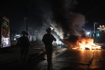 Israeli police patrol during clashes between Arabs, police and Jews, in the mixed town of Lod, central Israel.