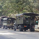 Soldiers sit inside trucks parked on a road in Naypyitaw, Myanmar,