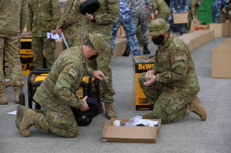 Sappers Mark Weston and Stephen Mullett from the 22nd Engineer Regiment prepare generators to distribute among affected communities, in support to the Victorian Government's recovery efforts across the state, at the CFA State Logistic Centre in Melbourne.