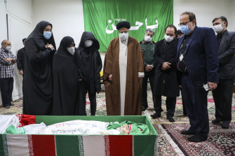 Iran's Judiciary Chief Ayatollah Ebrahim Raisi pays his respect to the body of slain scientist Mohsen Fakhrizadeh among his family, in Tehran, Iran, on Saturday.