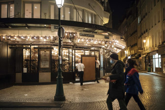 Waiters close a bar terrace in Paris. French restaurants, cinemas and theatres are trying to figure out how to survive a new curfew aimed at stemming the flow of record new coronavirus infections.