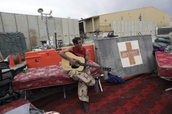 An Afghan soldier plays a guitar that was left behind after the American military departed Bagram air base.