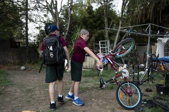 Jordan and Joel play with a bike before school in the backyard.