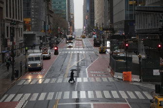 A pedestrian crosses 42nd Street in front of Grand Central Terminal during morning rush hour.