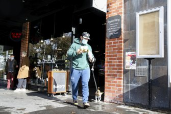A Sydney resident buys takeaway coffee from a Redfern cafe over the weekend.