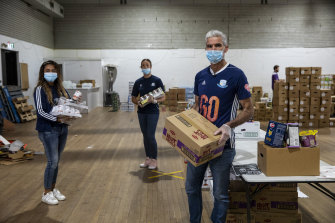 Craig Foster and Waverley Old Boys Football Club players Daen Medina (left) and Sandra Journot (middle) were packing boxes of essential goods for people in need on Wednesday at the Addi Road Food Pantry in Marrickville.