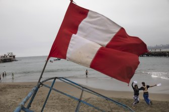 A Peruvian flag flies on the beach in Chorrillos, Lima, as a couple dances on the sand. More than 250 Chinese fishing vessels are operating just outside Peru's maritime zone.