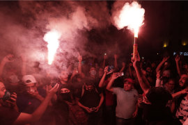 Protesters light flares in Beirut on Saturday night.