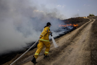 An Israeli firefighter attempts to extinguish a fire near Or HaNer Kibbutz caused by a balloon launched from the Gaza Strip on Wednesday.