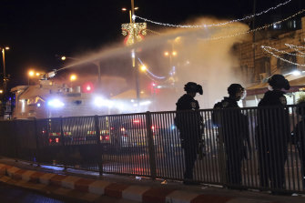 Israeli police use a water cannon to disperse Palestinian protesters from the area near the Damascus Gate in the Old City of Jerusalem.