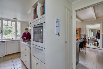Robin Mosman, at left, in her apartment's kitchen. The door into the kitchen of daughter Zoe's family is the junction between the two homes.