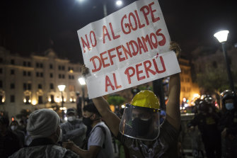 "A protester holds a banner that reads in Spanish: ""No to the coup, let's defend Peru,"" in favour of President Martin Vizcarra in Plaza San Martin in Lima."