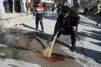 An Afghan man sweeps blood after gunmen fired on a car in northern Kabul on Sunday, killing two women judges who worked for Afghanistan's high court.