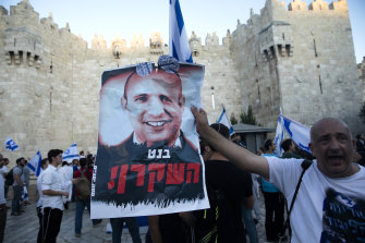 """A marcher holds a aposter with a photo of new Israeli Prime Minister Naftali Bennett with the word """"liar"""" in Hebrew, near the Damascus Gate on Tuesday."""