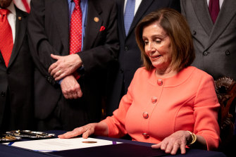 House Speaker Nancy Pelosi prepares to sign the official articles of impeachment.