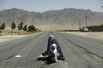 Afghanistan is falling into Taliban hands again. Here an Afghan woman begs for money on the Bagram-Kabul highway, north of Kabul.