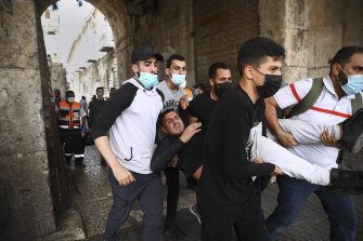 Palestinians evacuate a wounded protester during clashes with Israeli security forces at the Lions Gate in Jerusalem's Old City on Monday.