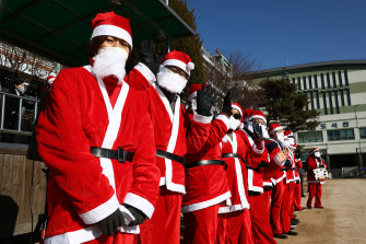 Gathering of more than four people are banned over Christmas and New Year holidays in Seoul. Pictured: South Korean Christian Santas get ready for drive-in religious service.