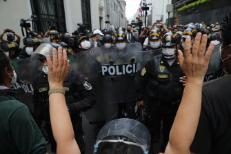 Police block supporters of former President Martin Vizcarra protesting near Congress while lawmakers swear-in Manuel Merino, head of Peru's legislature, as the new president in Lima on Tuesday.