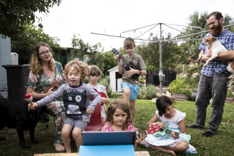 Hannah and Mark Tuton, with their children, learning to play the ukulele through an online lesson.