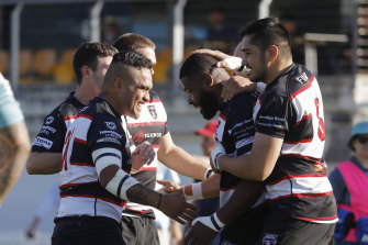 West Harbour players celebrate a try against Newcastle in the Shute Shield.
