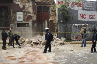 A policeman removes rubble from a building damaged by an earthquake in Oaxaca.