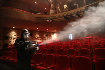 A disinfection worker wearing protective clothing sprays antiseptic solution in a theatre in Seoul.