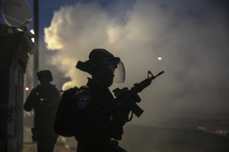 Israeli forces run during clashes with Israeli Arabs in the Israeli mixed city of Lod, Israel.