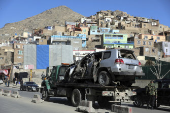 A damaged vehicle in a sticky bomb attack that killed a policeman is removed from the site in Kabul, Afghanistan, on Saturday.