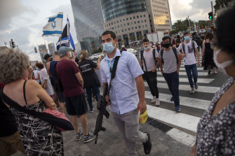 """An armed man with a face mask walks by Israeli protesters during """"Black Flag"""" protest against more virus restrictions by Israeli Prime Minister Benjamin Netanyahu in Tel Aviv on Monday."""