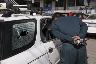 Police inspect the car where the assassination took place.