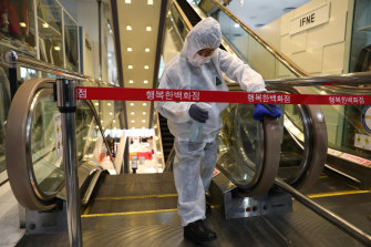 A worker sprays antiseptic solution on escalator handles at a department store in Seoul, South Korea.