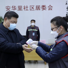 Chinese President Xi Jinping, left, wearing a protective face mask, receives a temperature check as he visits a community health center in Beijing on February 10.