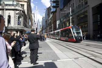 Onlookers were captivated by one of Sydney's new trams travelling along George Street for the first time during the day.