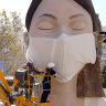 Workers place a mask on the figure of the Fallas festival in Valencia – the festival was cancelled because of the pandemic.